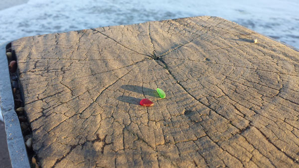 Red and green sea glass found at Southbourne Beach, Bournemouth