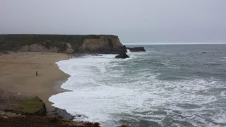 A view of Davenport Beach, California with waves crashing on the beach.