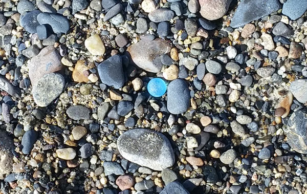 Light blue frosted sea glass marble resting on pebbles on Capo Beach, Dana Point
