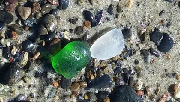 two pieces of bonfire sea glass on the sand in Capo Beach