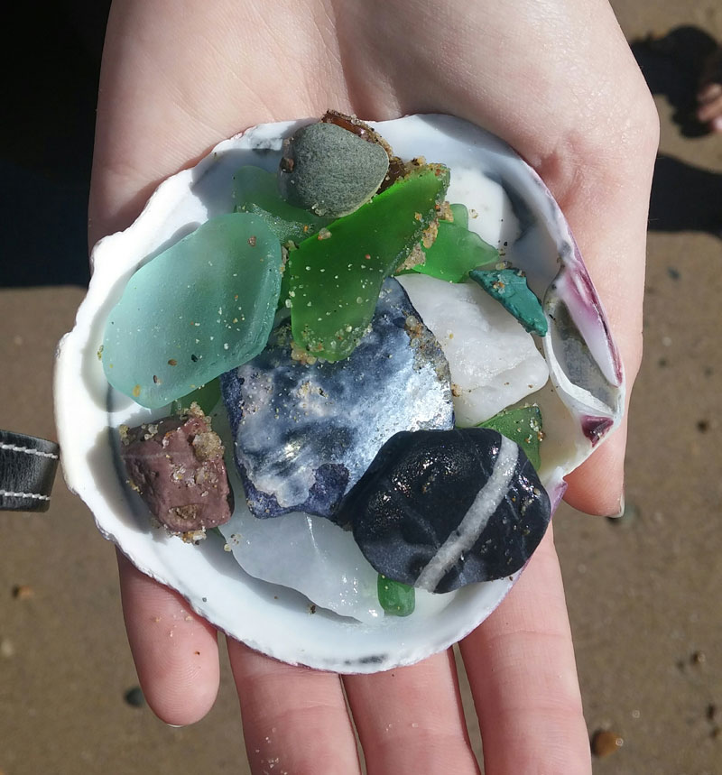 Girls hand holding a sea shell filled with green and blue sea glass in Laguna Beach.
