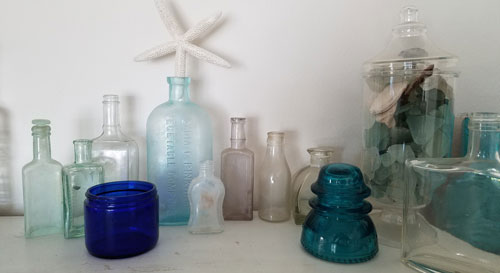 Various vintage medicine, perfume bottles and flasks as well as Noxzema face cream jar and a teal power insulator
