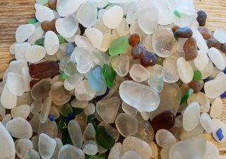 Image of more than 100 pieces of Glass Beach, Port Townsend, Washington sea glass on a wooden board.