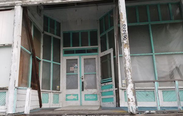 Large abandoned wooden house or store building with fun turquoise fish painted on the doors from the 1940's on Bush Point Beach, Whidbey Island, Washington front image.