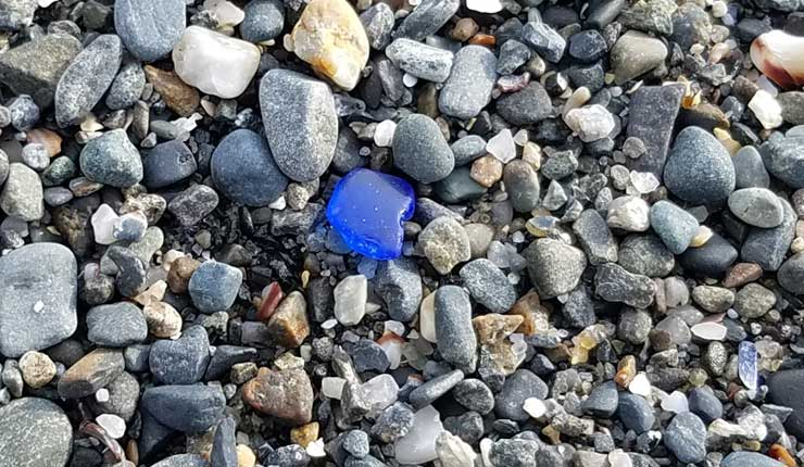 Smooth piece of wave tumbled blue sea glass washed up on pebbles at East Point Beach, Maine.